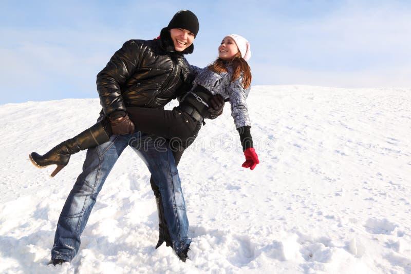 O homem e a menina dançam na área nevado e no sorriso imagens de stock