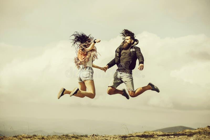 O homem e a menina saltam altamente foto de stock