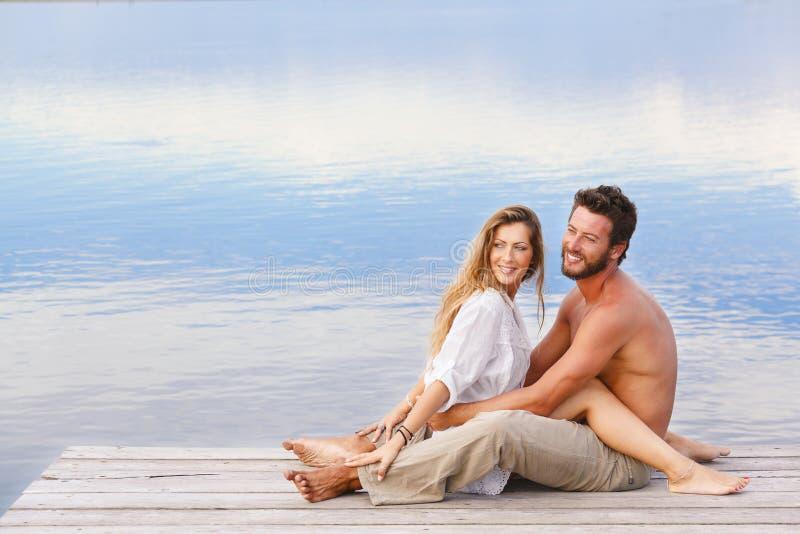 O homem e a mulher acoplam o assento em um molhe em um beira-mar fotos de stock royalty free