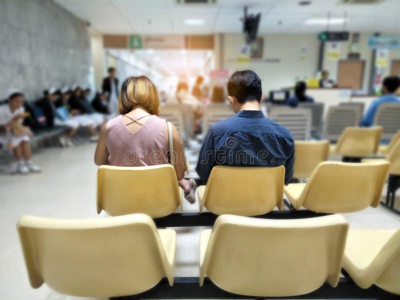 O homem e a mulher adultos sentam-se na espera inoxidável amarela da cadeira médica e nos serviços sanitários ao hospital imagens de stock royalty free