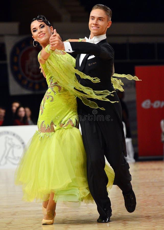 O homem e a mulher bonitos executam o sorriso durante a competição do dancesport fotografia de stock