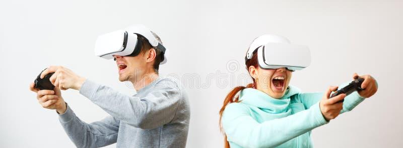 O homem e a mulher com os auriculares da realidade virtual est?o jogando o jogo foto de stock royalty free