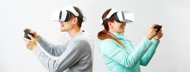O homem e a mulher com os auriculares da realidade virtual est?o jogando o jogo fotos de stock