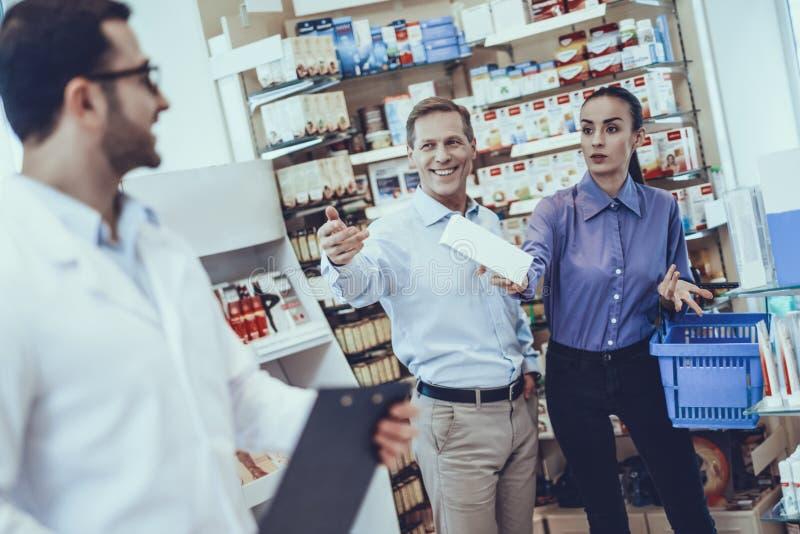 O homem e a mulher compram medicamento na farmácia foto de stock