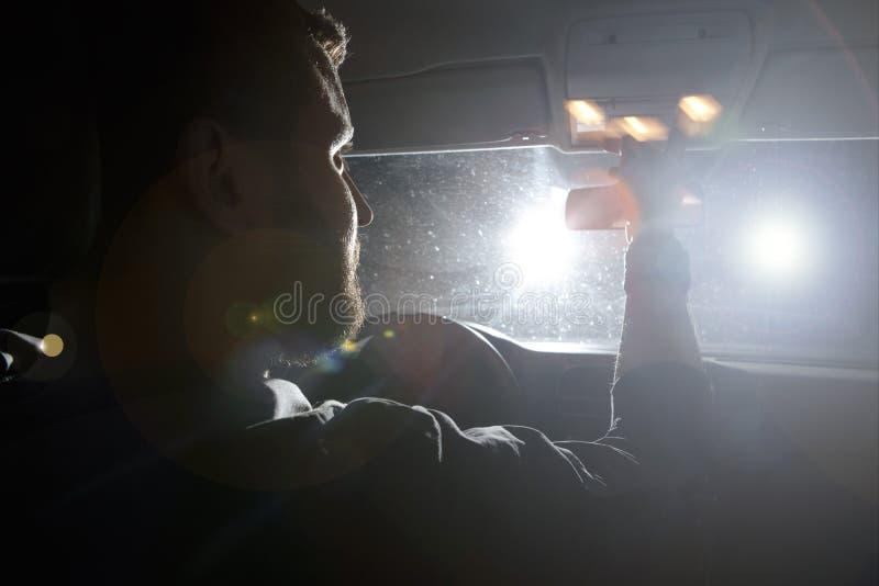 O homem e a mulher conduzem um carro na situação de emergência Noite da noite fotografia de stock royalty free