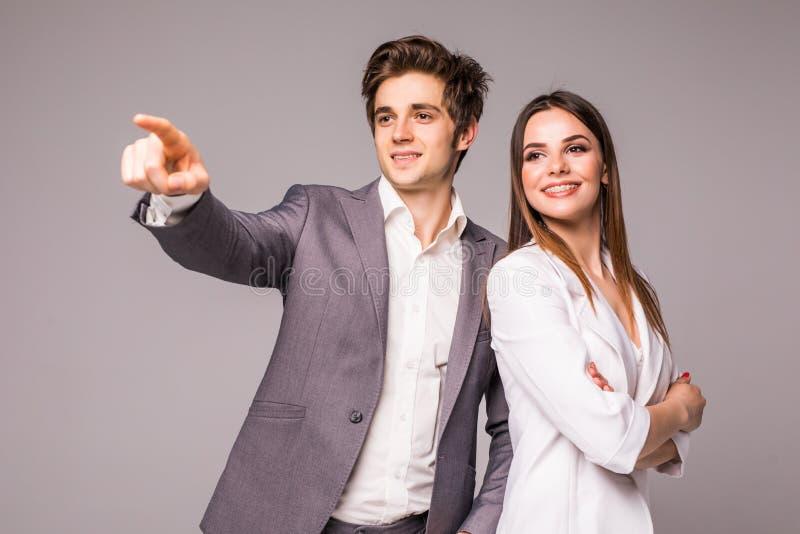 O homem e a mulher de negócio em um fundo cinzento Homem aguçado afastado no cinza foto de stock royalty free