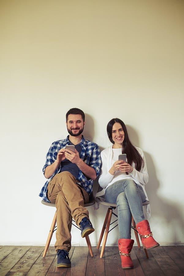 O homem e a mulher de sorriso estão sentando-se em cadeiras com smartphones imagens de stock