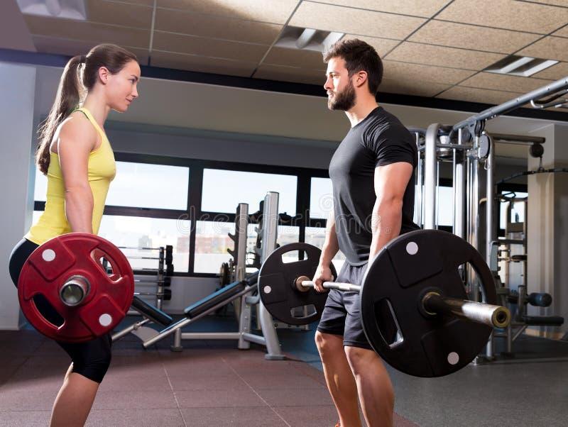 O homem e a mulher do Barbell malham no gym da aptidão imagens de stock royalty free
