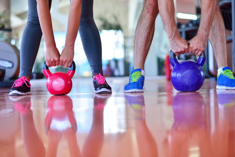 O homem e a mulher do exercício do balanço de Kettlebells malham no gym imagem de stock