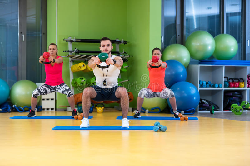 O homem e a mulher do exercício do balanço de Kettlebells malham no gym fotografia de stock royalty free