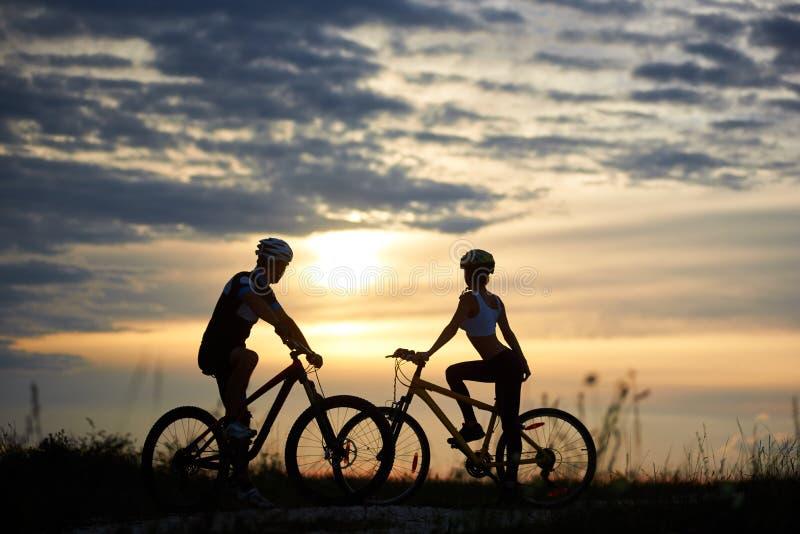 O homem e a mulher em bicicletas estão na estrada oposto a se e olham para tomar partido por do sol fotos de stock royalty free