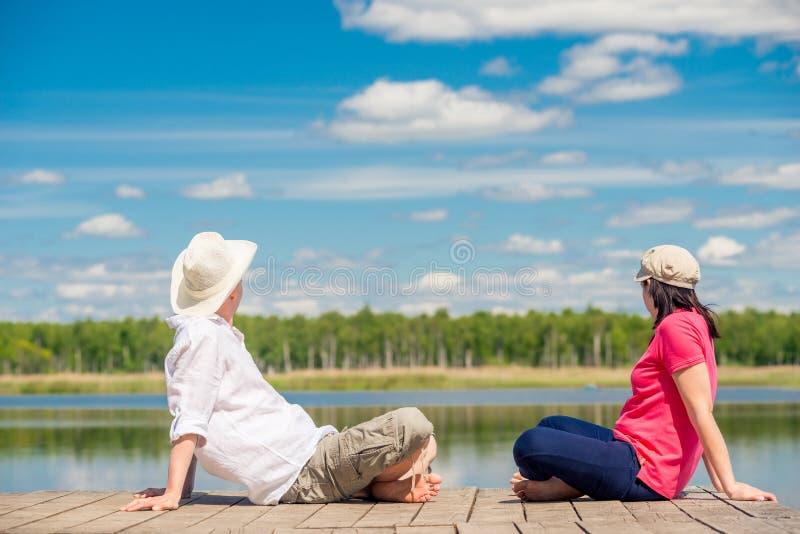 O homem e a mulher em um cais de madeira sentam-se fotos de stock
