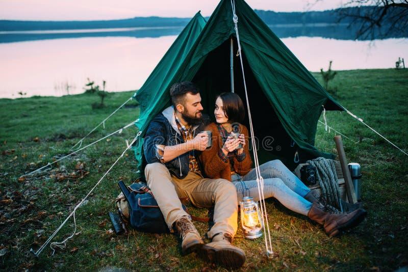 O homem e a mulher em uma barraca guardam uma lanterna elétrica imagens de stock royalty free