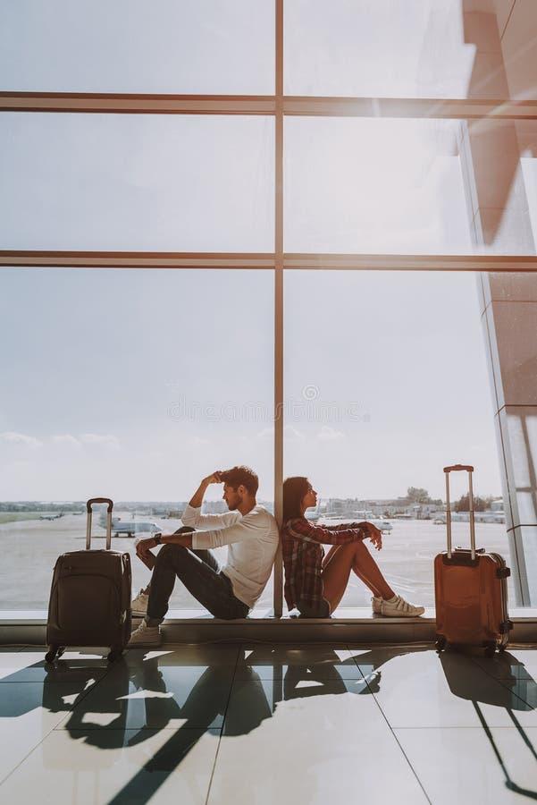 O homem e a mulher estão esperando o voo imagem de stock