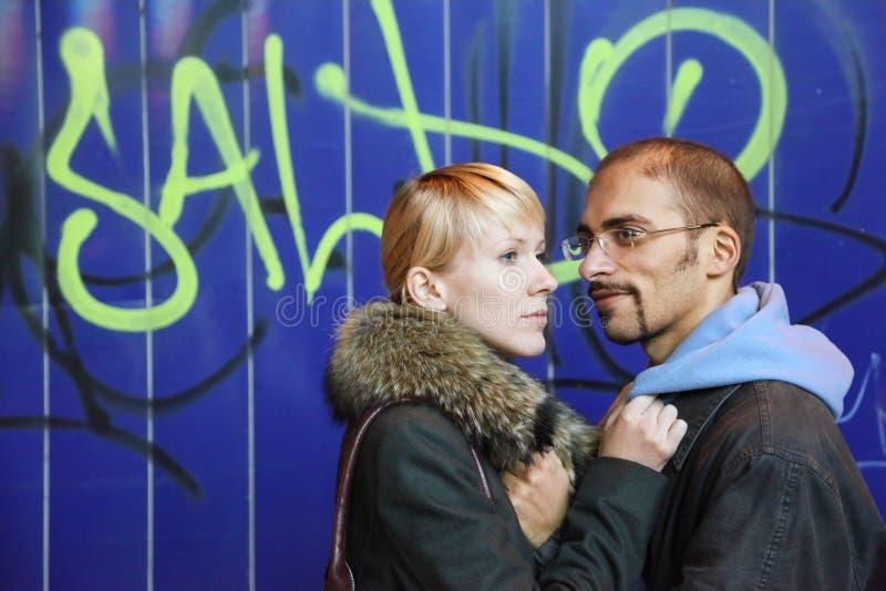 O homem e a mulher estão permanecendo a parede próxima dos grafittis fotografia de stock royalty free