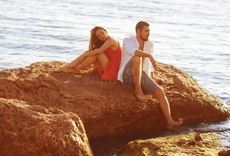 O homem e a mulher estão sentando-se em uma pedra do sofrimento imagem de stock royalty free