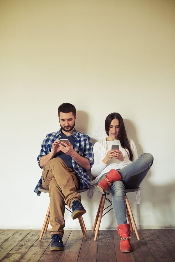 O homem e a mulher estão trabalhando em seus smartphones imagem de stock royalty free