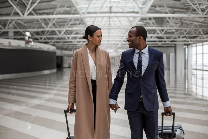 O homem e a mulher felizes estão andando no terminal fotos de stock