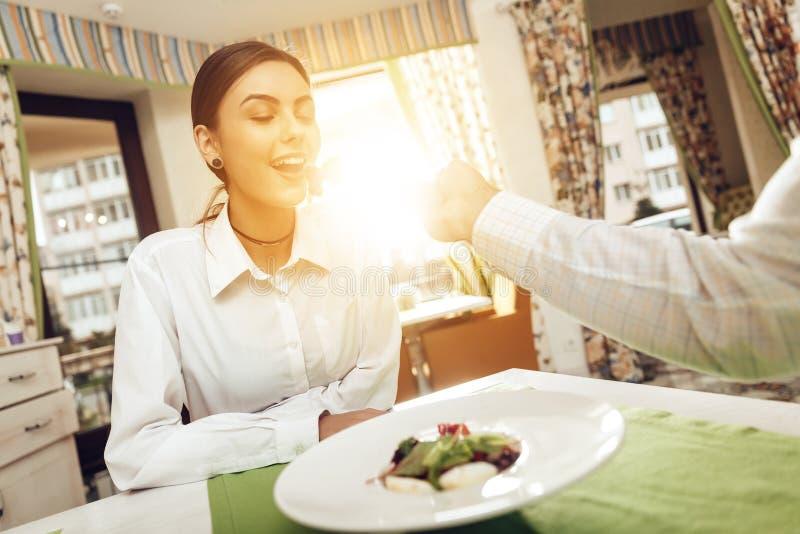 O homem e a mulher felizes têm o almoço em um restaurante fotos de stock royalty free