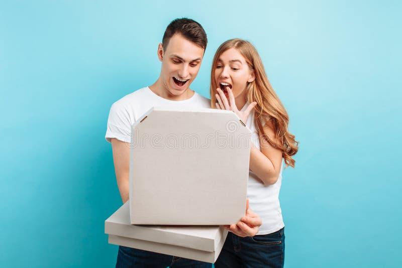 O homem e a mulher, guardam caixas com pizza italiana, relaxam em um fundo azul fotografia de stock royalty free