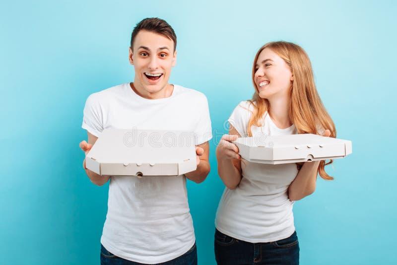 O homem e a mulher, guardam caixas com pizza italiana, relaxam em um fundo azul foto de stock
