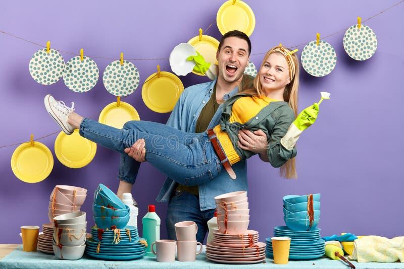 O homem e a mulher loucos obtêm o prazer dos pratos de lavagem imagens de stock