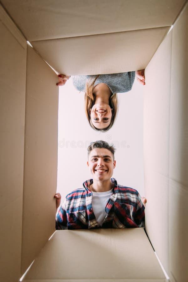 O homem e a mulher loving olham em umas caixas movendo-se Vista do interior da caixa fotografia de stock