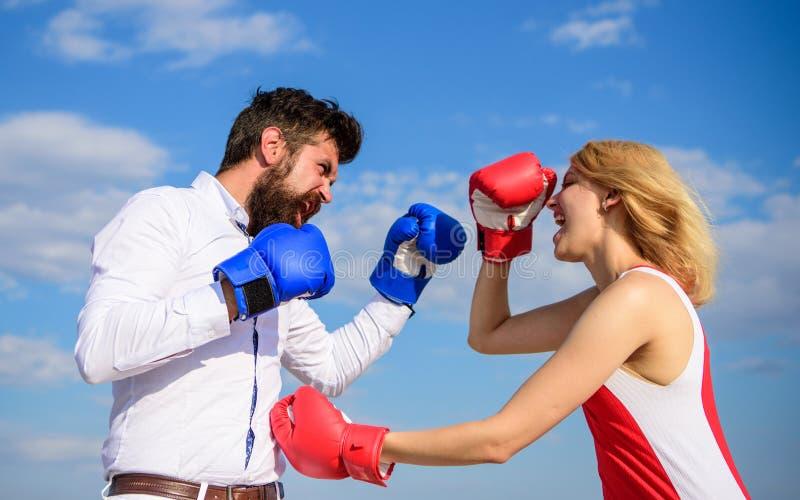 O homem e a mulher lutam o fundo do céu azul de luvas de encaixotamento Defenda sua opinião na confrontação Pares na luta do amor fotografia de stock royalty free