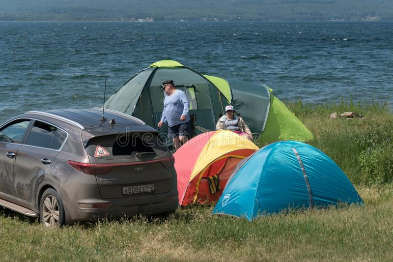 O homem e a mulher relaxam em um acampamento da barraca na costa de um grande lago na temporada de verão imagem de stock royalty free