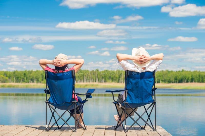 o homem e a mulher relaxam em um cais perto de um assento do lago fotos de stock