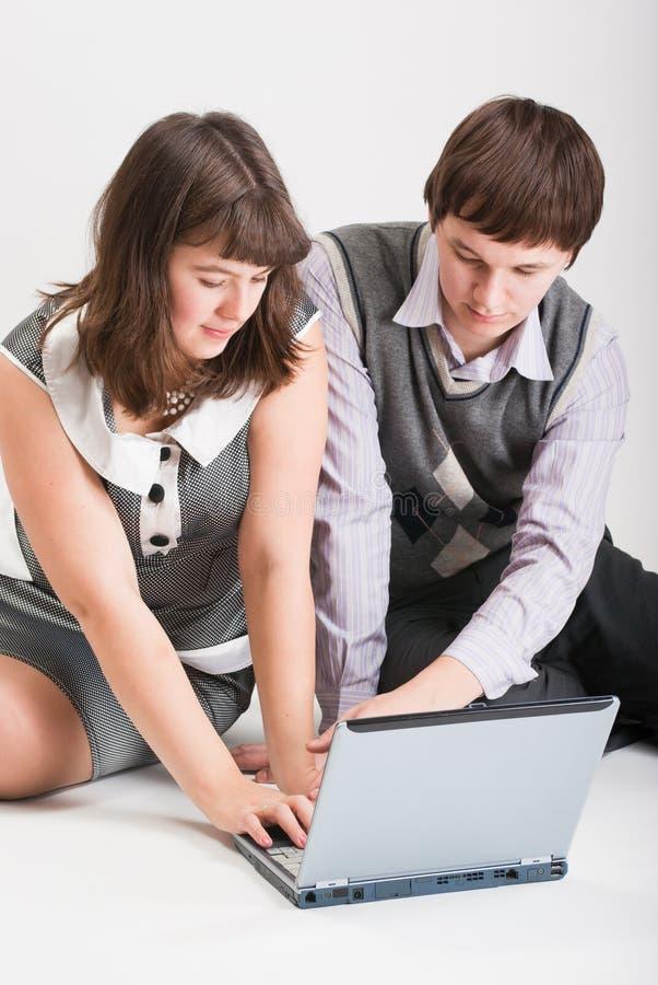O homem e a mulher trabalham junto no computador fotos de stock
