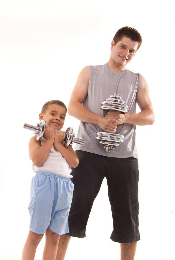 O homem e o filho exercitam na ginástica fotos de stock