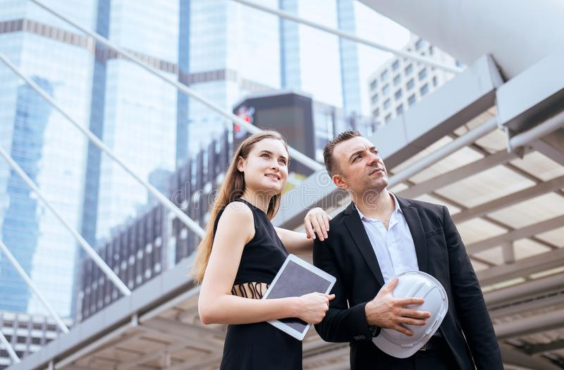O homem e os coordenadores bem sucedidos fêmeas que trabalham no terreno de construção, começam acima o projeto novo imagens de stock