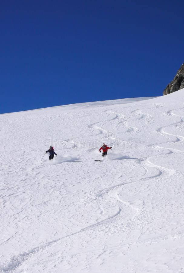 O homem e os esquiadores backcountry fêmeas tiram primeiras trilhas na neve fresca do pó nos cumes imagem de stock royalty free