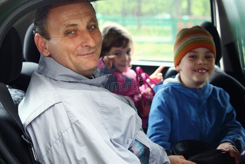 O homem e os miúdos sentam-se no carro imagens de stock royalty free