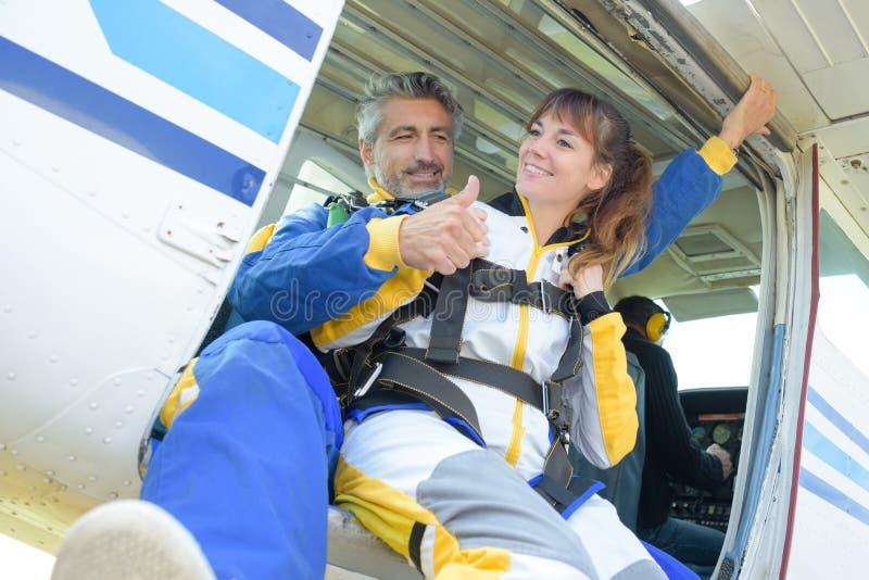 O homem e a senhora poised para fazer o tandem saltam em queda livre fotos de stock royalty free