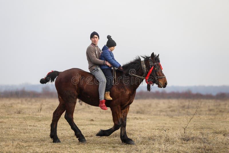 O homem e seu filho são em pelo montando um cavalo decorado antes de um celebrati do esmagamento foto de stock