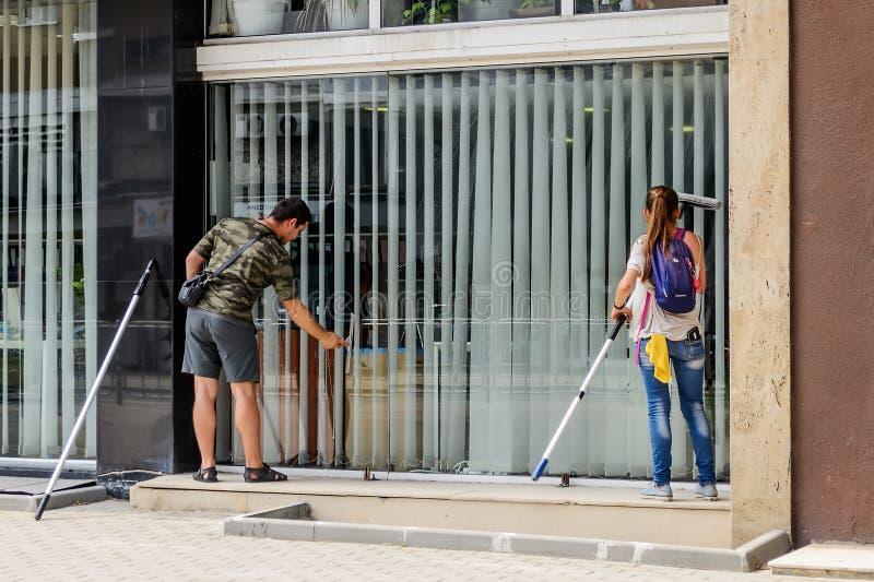 O homem e uma mulher com espanadores lavam uma grande janela do escritório no primeiro andar de uma construção do lado da rua Pov fotografia de stock royalty free
