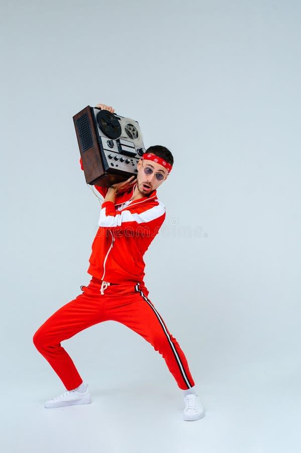 O homem elegante alegre que veste uma dança vermelha do terno dos esportes salta com um gravador retro estilo interessante e ferv foto de stock royalty free