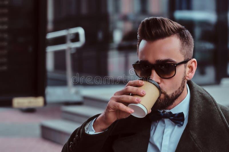 O homem elegante atrativo nos óculos de sol está bebendo seu café ao sentar-se fora no coffeeshop fotos de stock