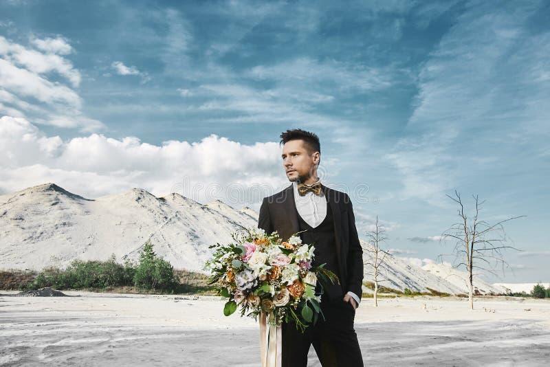O homem elegante considerável novo no terno elegante e no laço está guardando um ramalhete grande das flores e dos olhares para t imagens de stock