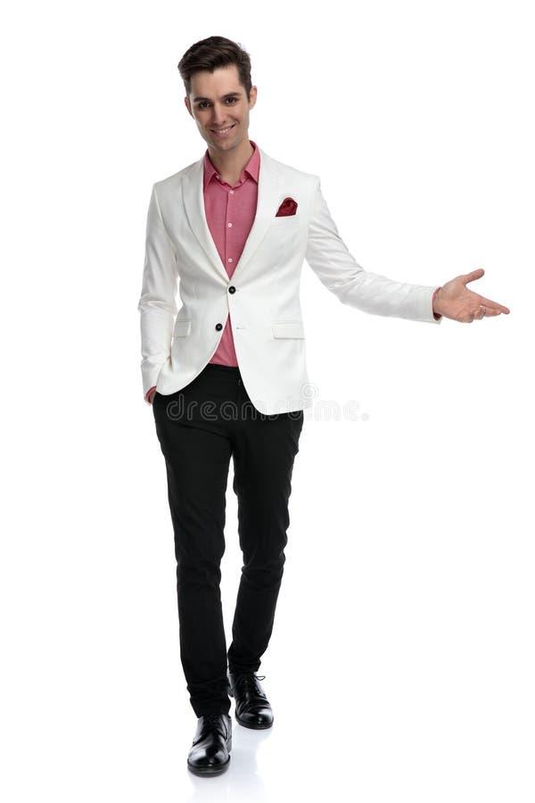 O homem elegante novo de sorriso convidar caminhadas do quando imagem de stock royalty free