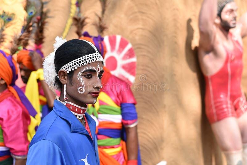 O homem em étnico indiano tradicional compõe o vestuário, apreciando a feira
