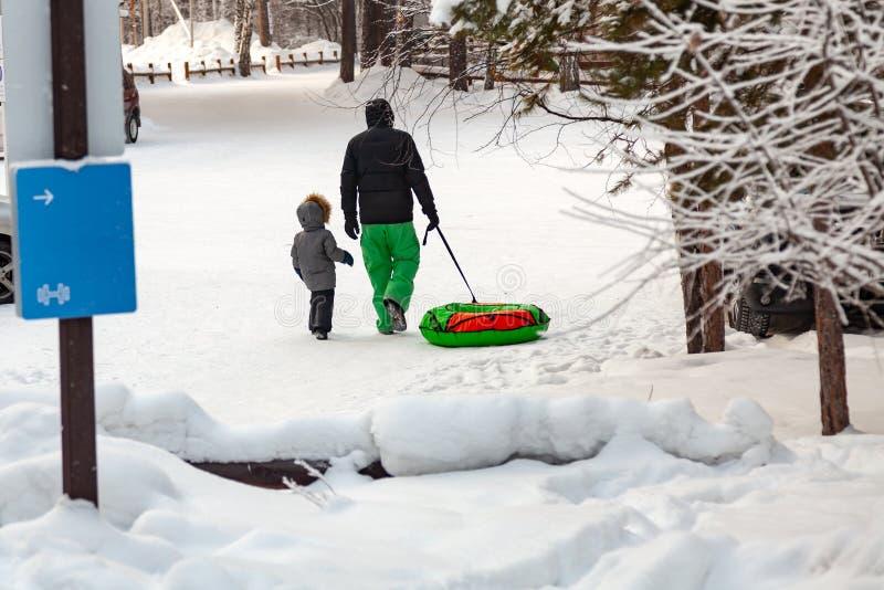 O homem em calças verdes com seu filho para passar o fim de semana nas madeiras vai para uma movimentação no monte e puxa os tren fotos de stock