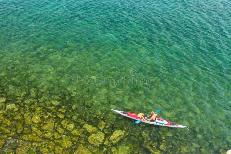 O homem em um caiaque do mar no Lago Baikal fotografia de stock