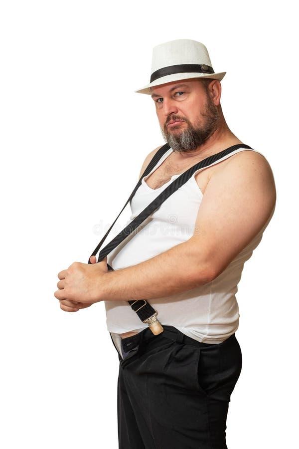 O homem em um chapéu e em um t-shirt atrasa os suspensórios que mostram sua brutalidade fotografia de stock royalty free