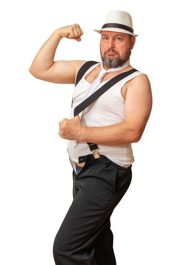 O homem em um chapéu e em uma camisa com uma barriga de cerveja dobrou sua mão que mostra h imagens de stock royalty free