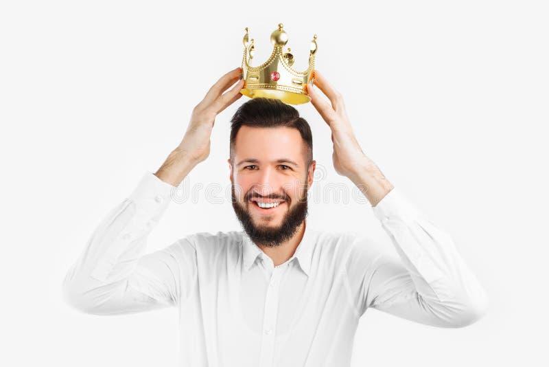 O homem em um fundo branco veste uma coroa em sua cabeça, em um estúdio da foto foto de stock
