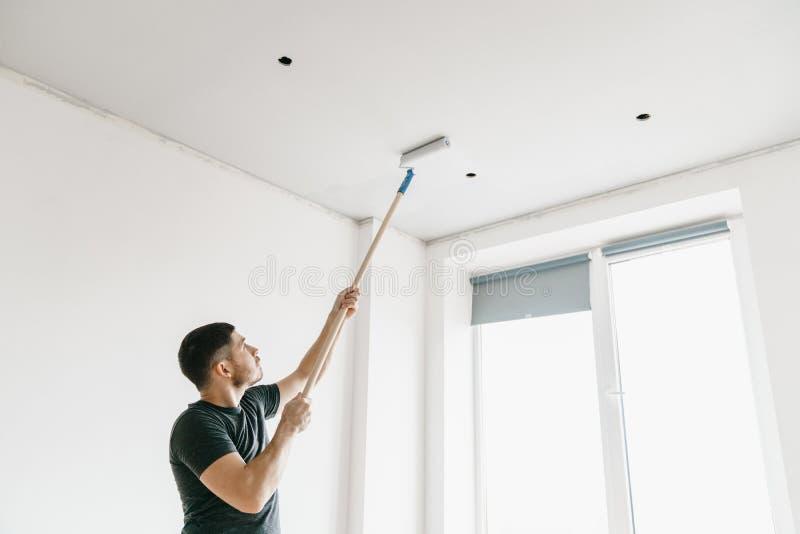 O homem em um t-shirt cinzento com um rolo em uma vara longa pinta o teto no cinza em casa imagem de stock