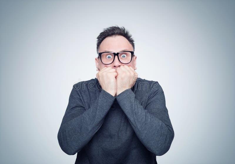 O homem em um t-shirt preto e em vidros é muito assustado Emoção profunda do conceito do medo foto de stock